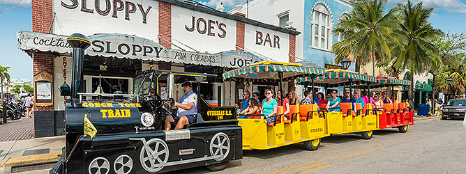 Image of Conch Tour Train and Guests driving past sloppy joes bar restaurant