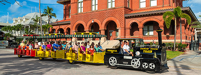 Image of Key West Sightseeing Tour train driving past customs house